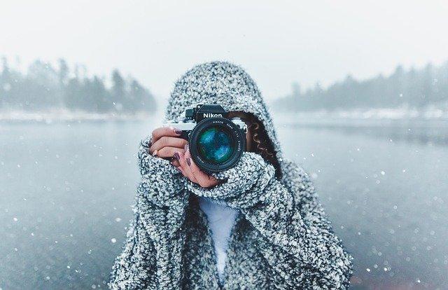 femme qui prend en photo de face avec de la neige en fond